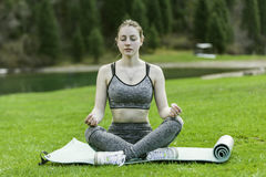 Meditation on a green lawn. The girl meditates, sits on a rug on a green lawn Stock Image