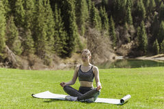 Meditation on a green lawn. The girl meditates, sits on a rug on a green lawn Stock Photography