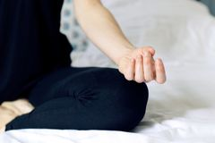 Meditation hand pose of a Zen Business woman doing yoga on bed relaxed in lotus gesture. Success executive manager escaping mental stress relaxing and doing yoga stock photo