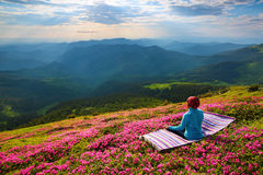 Meditation at the high mountains and sky with rays and clouds. On the lawn in pink rhododendrons the girl is sitting in lotus posture on the striped rug Stock Photos
