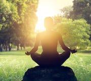 Meditation i parkera på solnedgångljus arkivfoto