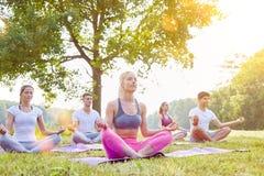 Meditation i yogagrupp i sommar royaltyfria bilder