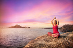 Meditation in India. Woman doing meditation in red costume on the stone near the ocean in Gokarna, Karnataka, India Royalty Free Stock Photos