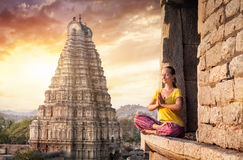 Meditation in India. Woman with Namaste mudra sitting near Virupaksha temple in Hampi, Karnataka, India Royalty Free Stock Image