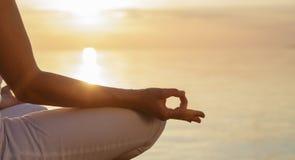 meditation Körperteil einer Frau im Lotussitz, Finger mudra gegen den Sonnenuntergang und ruhiger See lizenzfreies stockfoto