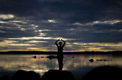 Meditation at a lake. Young woman making yoga exercise on a swedish lake in the sunset. Relaxing mood Royalty Free Stock Image