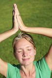 Meditation on a Lawn. Woman in green meditating on a lawn Royalty Free Stock Images