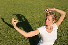 Meditation on a Lawn. Woman in white meditating on a green lawn Stock Photos