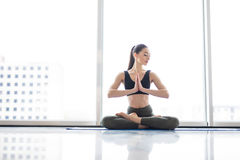 Meditation lotus pose. Young woman practicing flexible yoga pose against panoramic windows on city background royalty free stock images