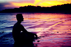 Meditation man. Man in meditation under the setting sun Royalty Free Stock Image
