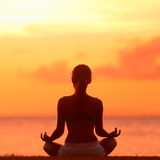 Meditation - Meditating yoga woman at beach sunset Stock Photos