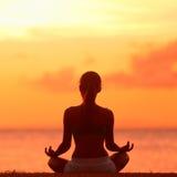 Meditation - meditera yogakvinnan på strandsolnedgången Arkivfoton