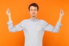 Meditation, mental practice. Young adult man closed eyes and doing yoga. Studio shot, orange background stock photography