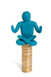 Meditation about money. Plasticine yogi sit on heap of coins isolated on white stock photos