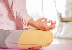 meditation A mulher está praticando o assento da ioga na pose de Lotus em casa foto de stock