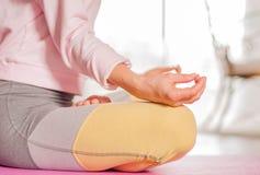 meditation A mulher est? praticando o assento da ioga na pose de Lotus em casa fotografia de stock