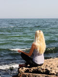 Meditation nahe dem Meer Stockfoto