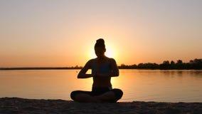 Meditation nahe dem Meer und Handelnyoga auf einem Strand bei Sonnenuntergang