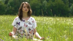 Meditation outdoors in green flower field, young woman sits in lotus position stock video footage