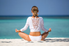 Meditation. Photo of a woman who is sitting in the lotus position on the ocean coast. Maldives Royalty Free Stock Image