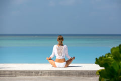 Meditation. Photo of a woman who is sitting in the lotus position on the ocean coast. Maldives Royalty Free Stock Images