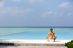 Meditation. Photo of a woman who is sitting in the lotus position on the ocean coast. Maldives Royalty Free Stock Photos