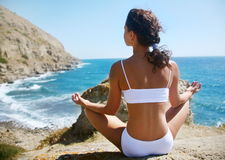 Meditation on a rocky seashore Stock Photography