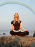 Meditation at the seashore under rainbow Stock Image