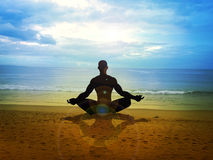 Meditation. Silhouette of a male figure meditating on the beach Royalty Free Stock Photo