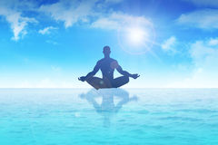 Meditation. Silhouette of a man figure meditating on water Stock Photography