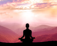 Meditation. Silhouette of man in the mountain Stock Photos
