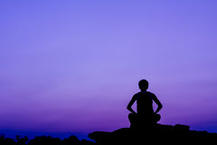 Meditation. Silhouette of a man in meditation posting Stock Image