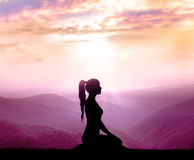Meditation. Silhouette of woman in mountains. Royalty Free Stock Images