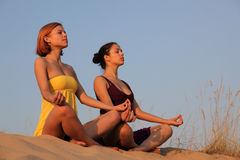Meditation of sisters. Two happy sisters sitting on a beach in a meditation/praise pose Royalty Free Stock Images
