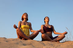 Meditation of sisters. Two happy sisters sitting on a beach in a meditation/praise pose on a decline Stock Photo