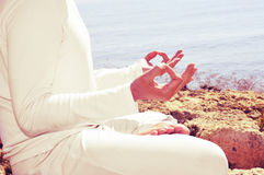 Meditation. Someone meditating in front of the sea, with a retro effect Stock Images