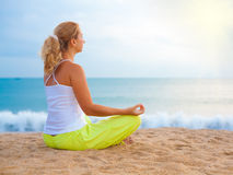 Meditation at sunrise time. Young beautiful  woman meditating on sunrise time Royalty Free Stock Photos
