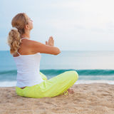 Meditation at sunrise time. Young woman meditating at sunrise time near the ocean Royalty Free Stock Image