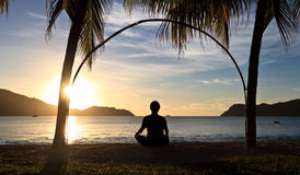 Meditation on sunset. Man silhouette on the island beach at sunset Royalty Free Stock Photo