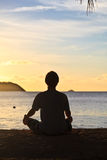 Meditation on sunset. Man silhouette on the island beach at sunset Royalty Free Stock Images