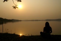 Meditation on Sunset at a lake. Silhouette meditation sunset at a lake shore Royalty Free Stock Photo