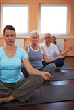 Meditation in tailor seat. Yoga group in gym doing meditation exercises Stock Images