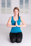 Meditation time. Young woman is doing some meditation in a white room Stock Photography