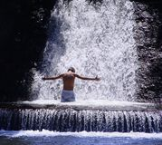 Meditation under waterfall. Young man relaxing under waterfall