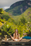 Meditation while on vacation in Hawaii. Spa vacation retreat woman relaxing at luxury travel resort. Happy blissful asian young woman in bikini in meditation Royalty Free Stock Images