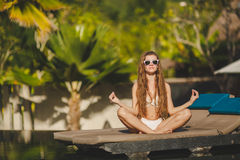 Meditation while on vacation in Hawaii. Spa vacation retreat woman relaxing at luxury travel resort. Happy blissful asian young woman in bikini in meditation Stock Images