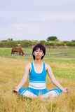 Meditation woman. Woman relaxes and meditates in peaceful field Royalty Free Stock Image