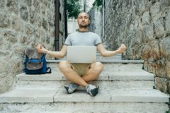 Meditation work. Freelancer man and a traveler working on a lapt Royalty Free Stock Photos