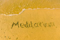 Meditation written on sand. Sandy beach with Meditation sign scribbled on beach sand. leisure time concept stock images