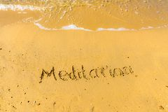 Meditation written on sand. Sandy beach with Meditation sign scribbled on beach sand. leisure time concept royalty free stock photography